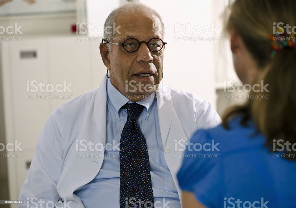 "Concerned Doctor Meeting with His Patient ""Mature Black medical doctor with a serious expression on his face, speaks to a female patient in his office. Horizontal shot."" Adult Stock Photo"