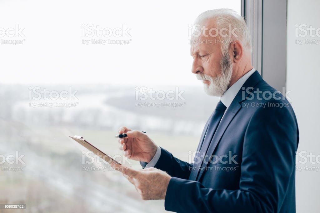 Anciano preocupado mirando documentación - Foto de stock de Adulto libre de derechos