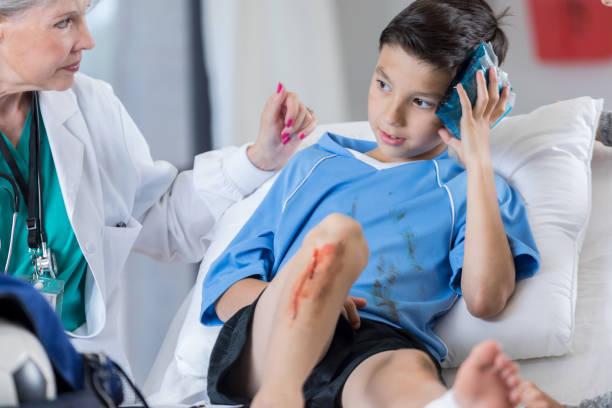 Urgentologue concerné examine un footballeur blessé - Photo