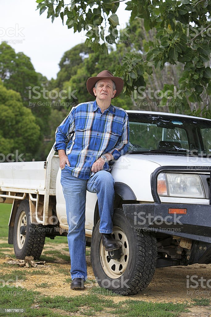 Concerned farmer leaning on farm vehicle stock photo