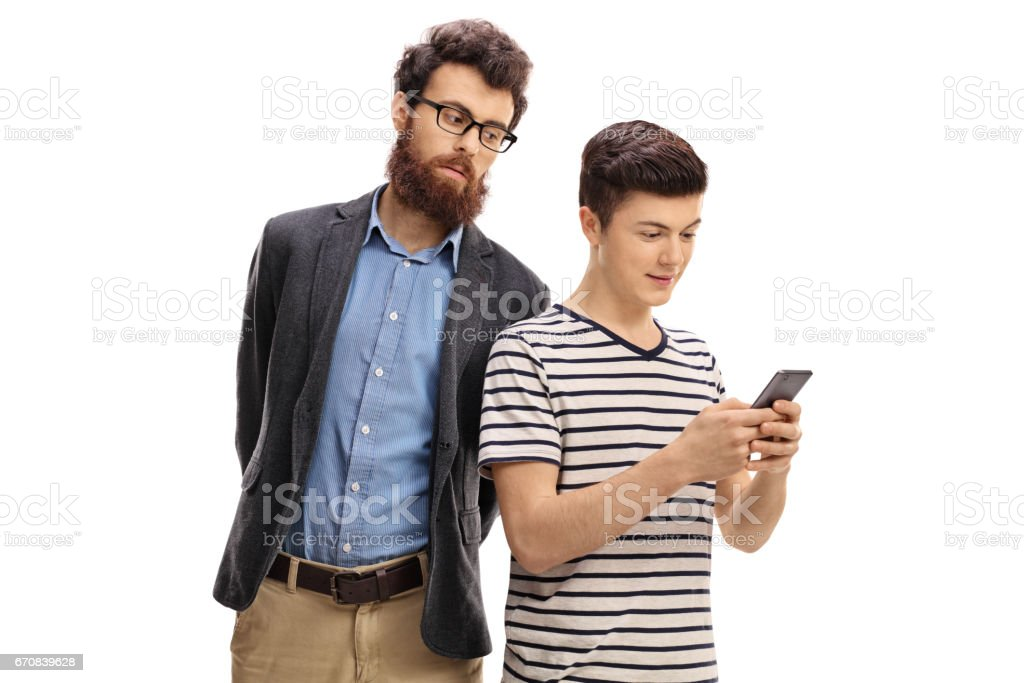 Concerned father peeking at the phone of his son stock photo