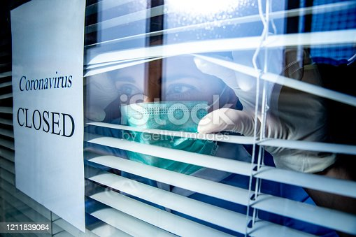 Concerned healthcare worker looking through a window with a Closed sign due to Coronavirus