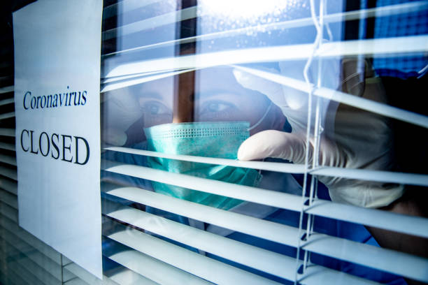 Concerned Healthcare worker looking through a window with a Closed sign due to Coronavirus stock photo