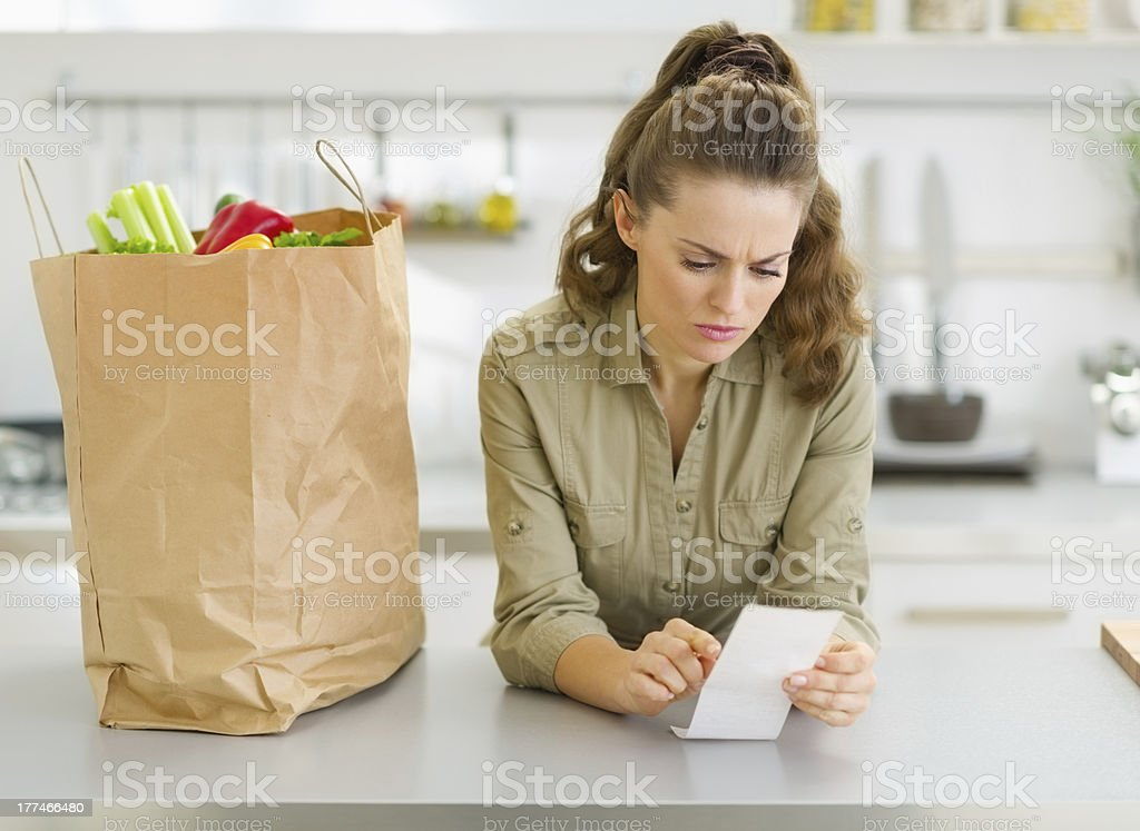 Concerned housewife checking bill after shopping in kitchen royalty-free stock photo