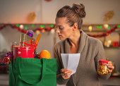 Concerned young housewife with checks exploring christmas purchases