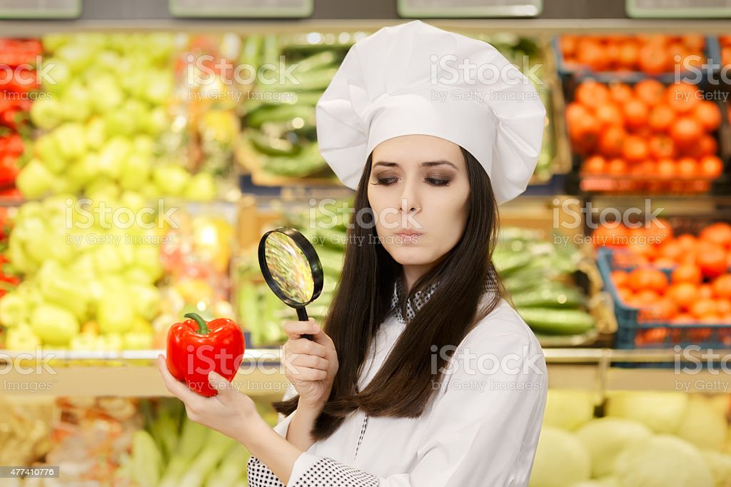 Concerned  Lady Chef Inspecting Vegetables with Magnifying Glass stock photo