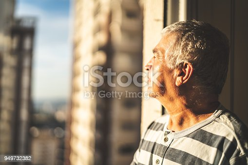 istock Concerned mature man looking through window 949732382