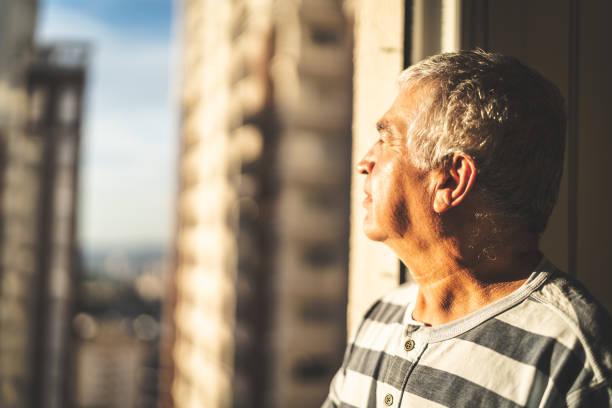 concerned mature man looking through window - old men window imagens e fotografias de stock