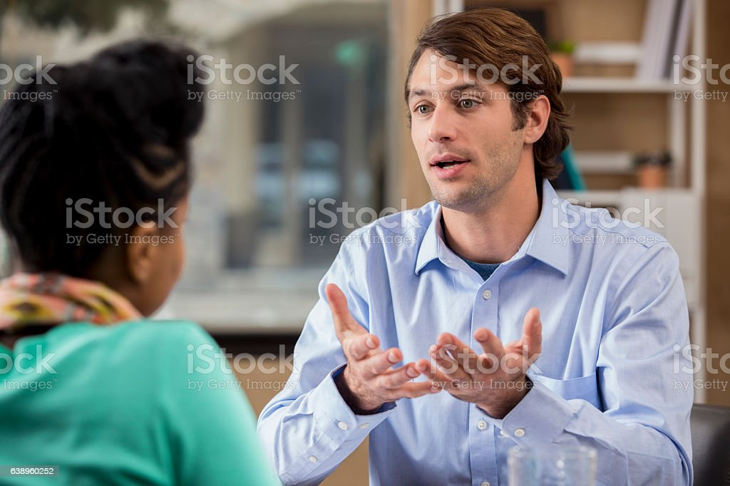 Concerned mid adult Caucasian counselor talks with patient stock photo