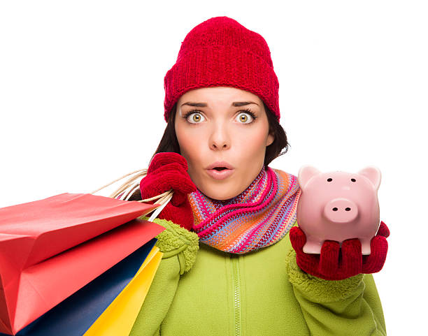 Concerned Mixed Race Woman Holding Shopping Bags and Piggybank Concerned Mixed Race Woman Wearing Winter Clothes Holding Shopping Bags and Piggybank Isolated on White Background. money to burn stock pictures, royalty-free photos & images