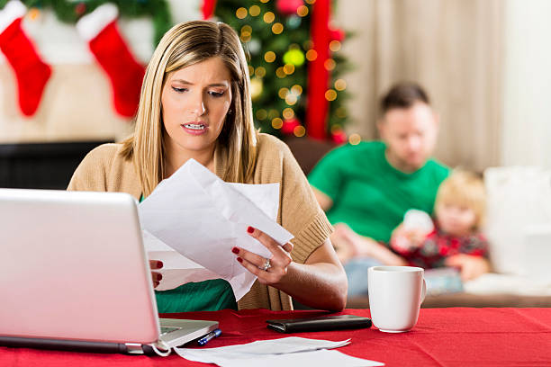 concerned mom looks through bills at christmas - holiday and invoice family foto e immagini stock