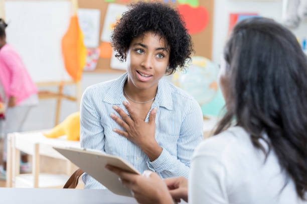 Concerned mom talks with her child's teacher stock photo