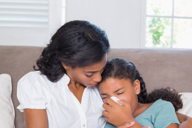 Concerned mother cuddling sick daughter Concerned mother cuddling sick daughter at home in living room human parainfluenza virus stock pictures, royalty-free photos & images