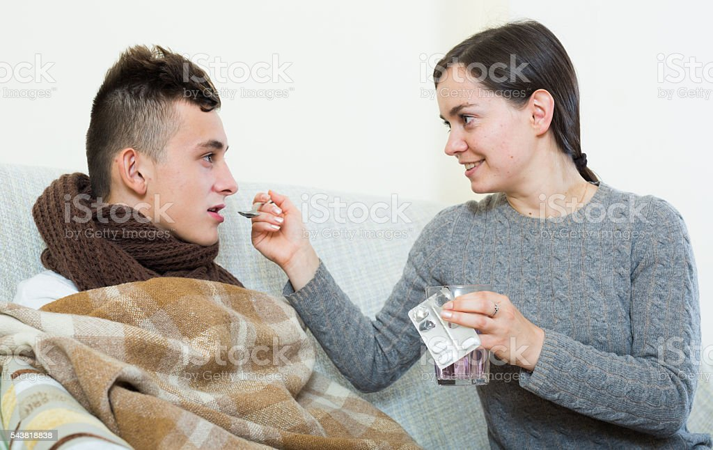 Concerned mother giving mixture to son with quinsy stock photo