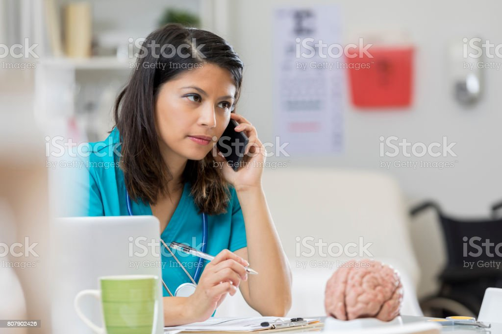 Concerned neurologist uses smart phone stock photo
