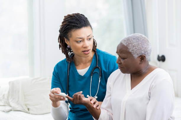 concerned nurse checks patient's blood sugar - diabetic stock photos and pictures