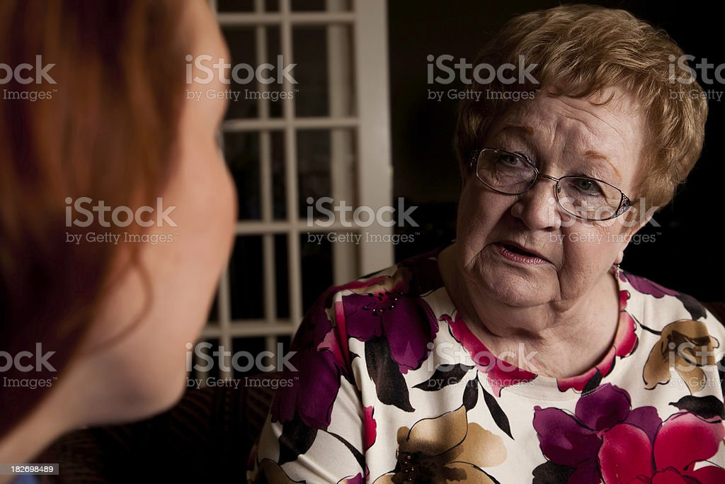 Concerned Senior Adult Having Serious Conversation With Young Woman royalty-free stock photo