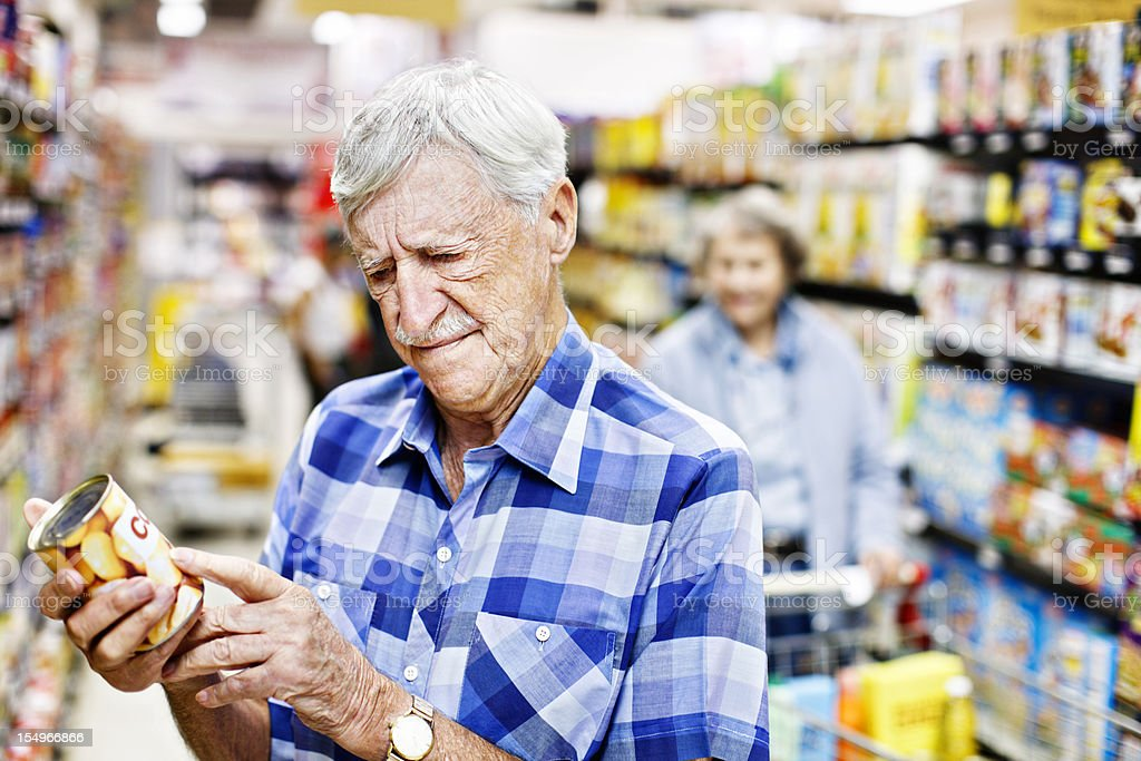 Concerned senior man checks can label in supermarket stock photo