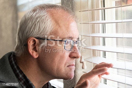 istock Concerned senior man looking through the window 1148272151