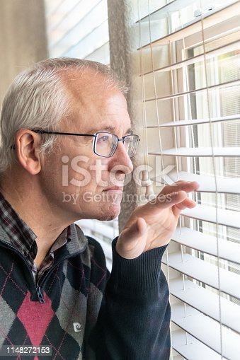 istock Concerned senior man looking through the window 1148272153