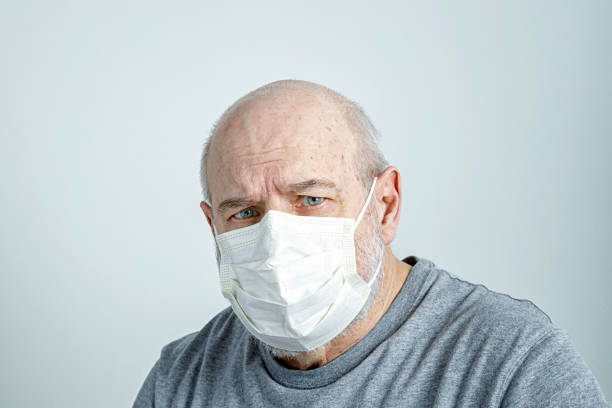 Concerned Senior Man Wearing Medical Surgical Face Mask stock photo
