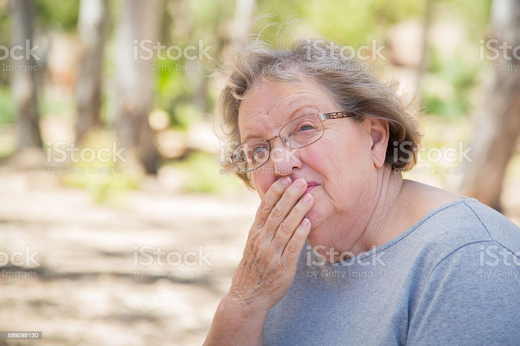 Concerned Senior Woman Sitting Alone stock photo
