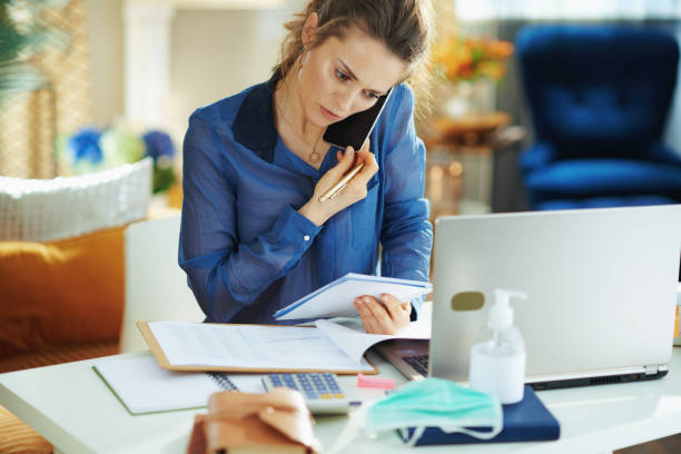 concerned trendy woman talking on phone and working stock photo