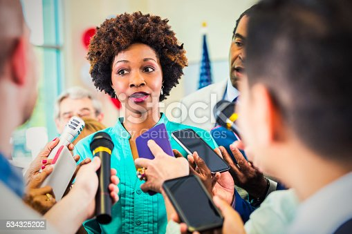 istock Concerned woman confronted by journalists 534325202