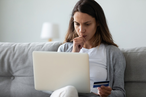 istock Concerned woman holding on lap computer in hand credit card 1192627597