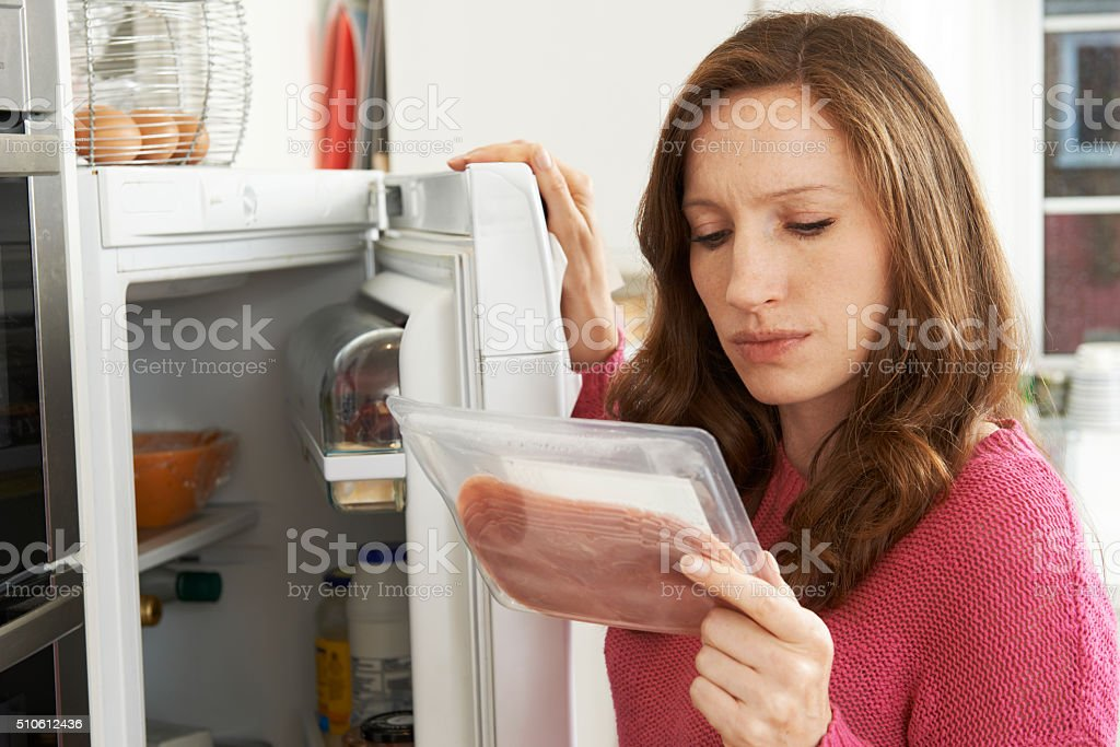 Concerned Woman Looking At Pre Packaged Meat stock photo