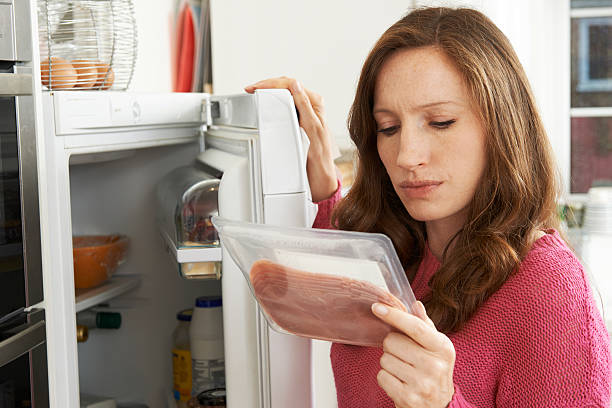 concerned woman looking at pre packaged meat - gemaksvoedsel stockfoto's en -beelden