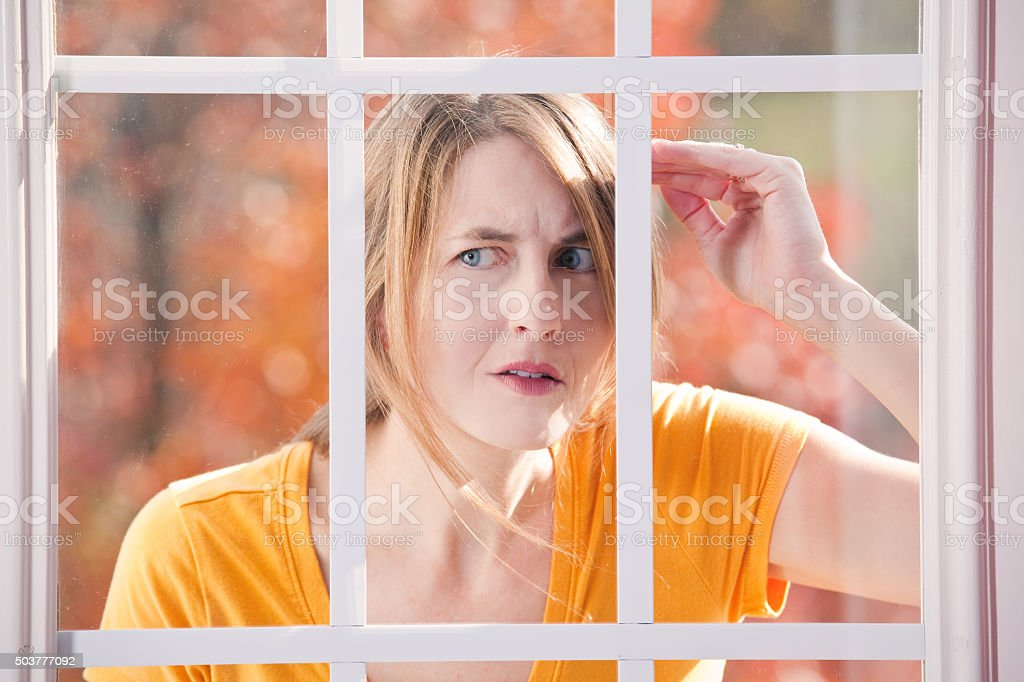 Concerned Woman Peeking In Someone's Window stock photo