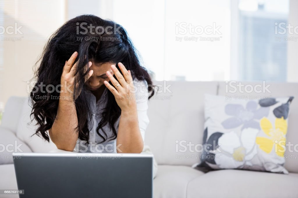 Concerned woman sitting at home foto stock royalty-free