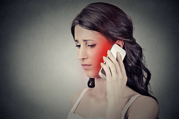 concerned woman talking on mobile phone having headache - strahlung stock-fotos und bilder