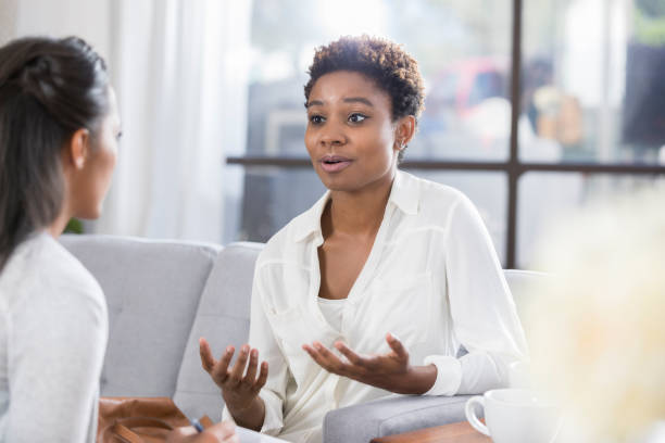 Concerned woman talks with therapist stock photo