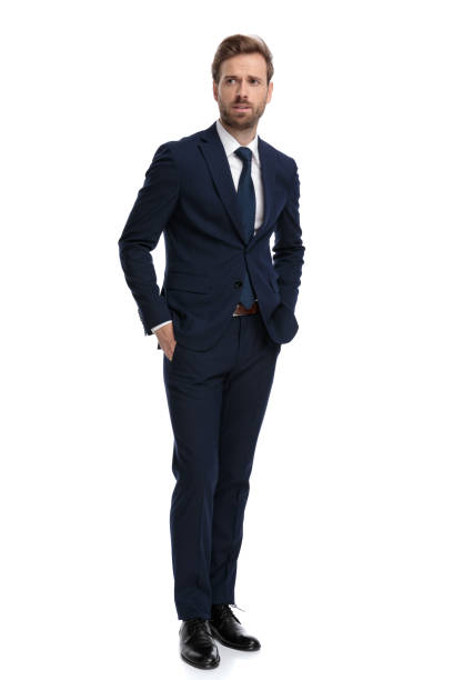 concerned young businessman holding hands in pockets concerned young businessman in navy blue suit holding hands in pockets, looking to side and walking isolated on white background, full body business suit stock pictures, royalty-free photos & images