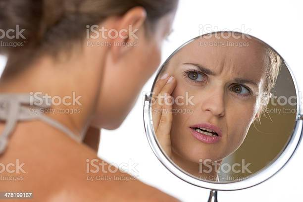 Concerned Young Woman Looking In Mirror Stock Photo - Download Image Now
