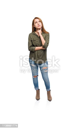 Full body shot of a concerned young woman standing isolated on a white background.