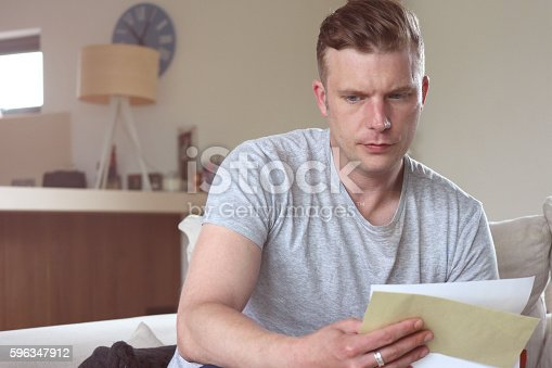 Mid shot of man reading a letter of worrying news