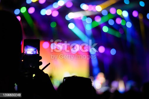 People at concert party, crowd at music festival. Rock concert. Fans holding smart phones and they enjoying at musical concert