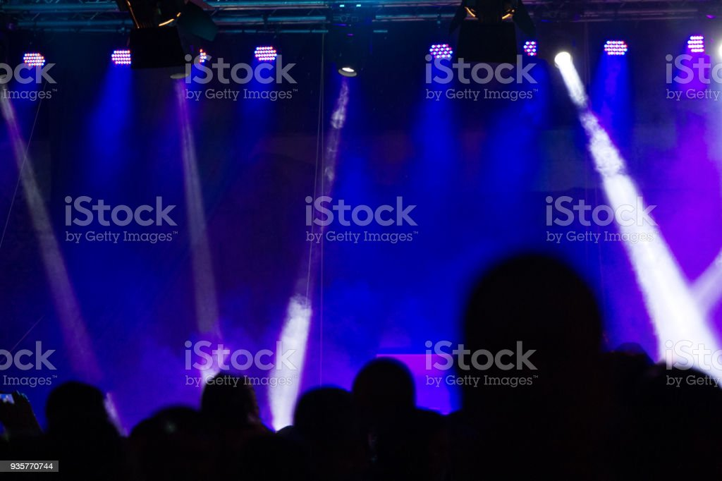 Concert crowd attending a concert, people silhouettes are visible, backlit by stage lights. Raised hands and smart phones are visible here and there. stock photo