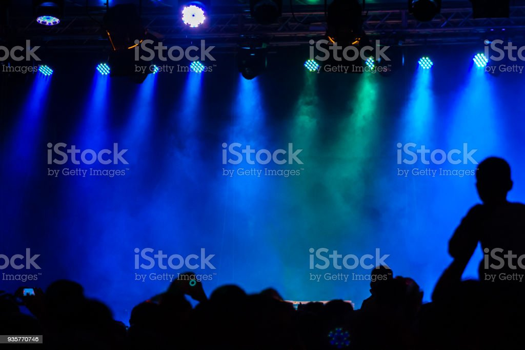 Concert crowd attending a concert, people silhouettes are visible, backlit by stage blue lights. Smart phones are visible here and there. stock photo