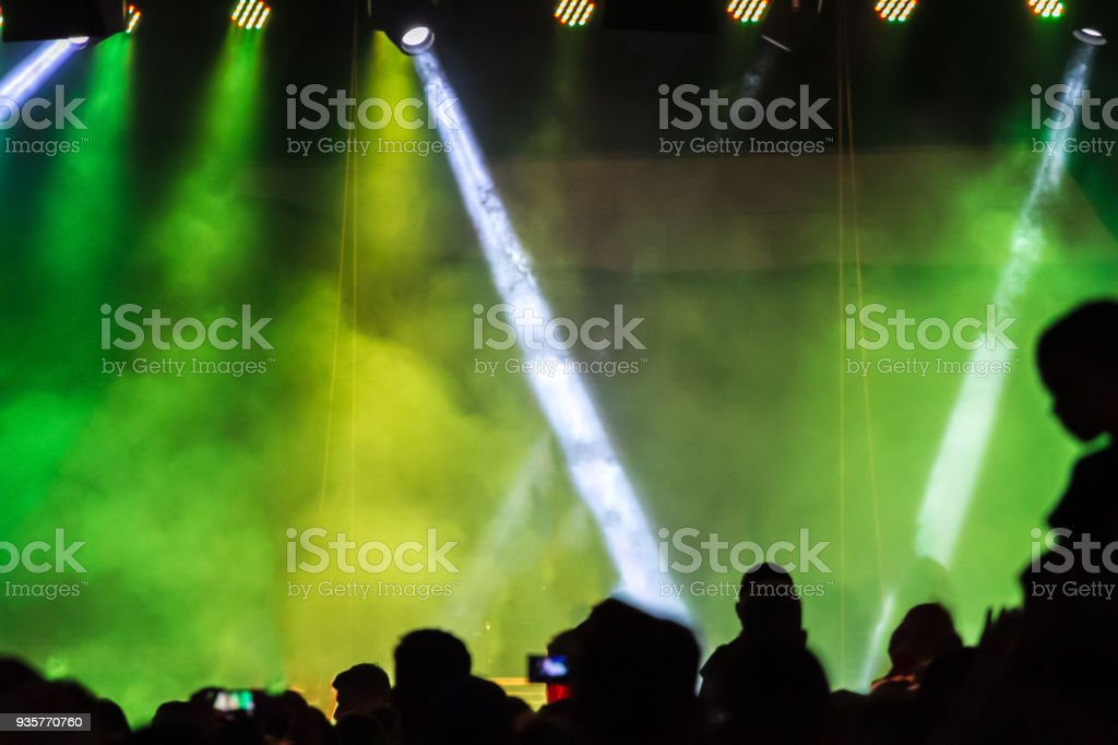 Concert crowd attending a concert, people silhouettes are visible, backlit by stage green lights. Smart phones are visible here and there. stock photo