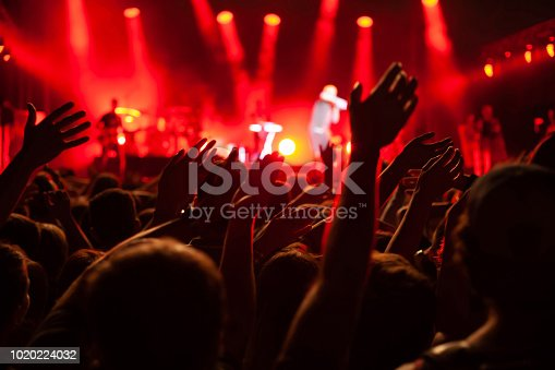 concert crowd during festival, hands of many people cheering musicians playing music on stage, red back light