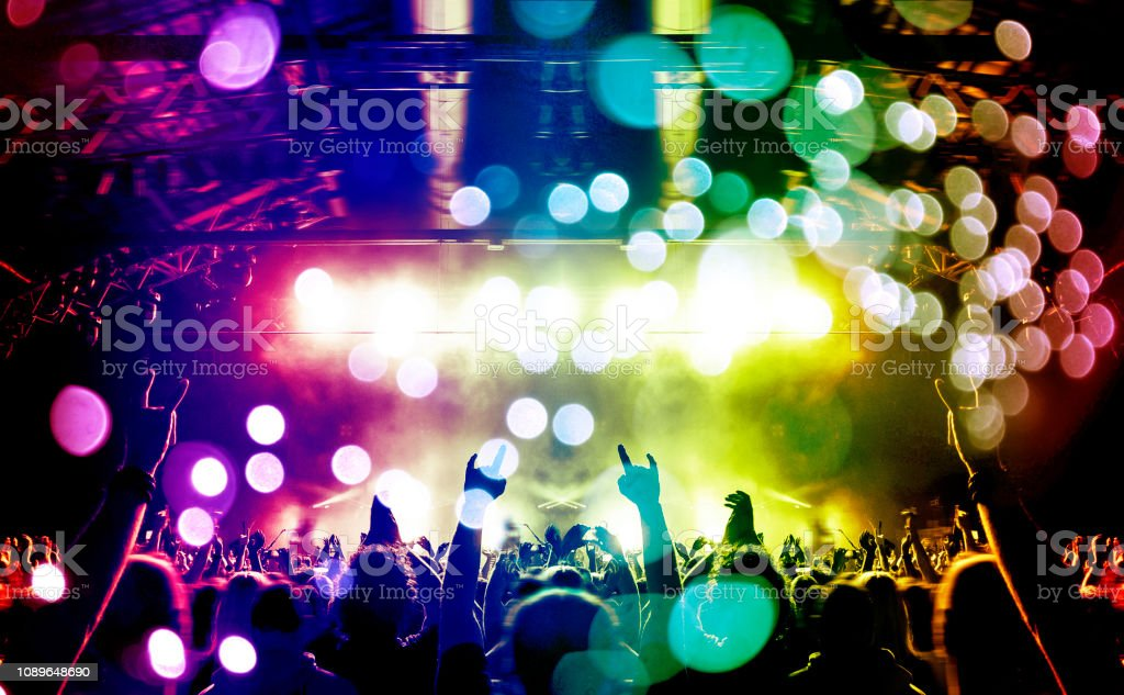 Concert hall crowded with people in front of a stage lit for the gig.