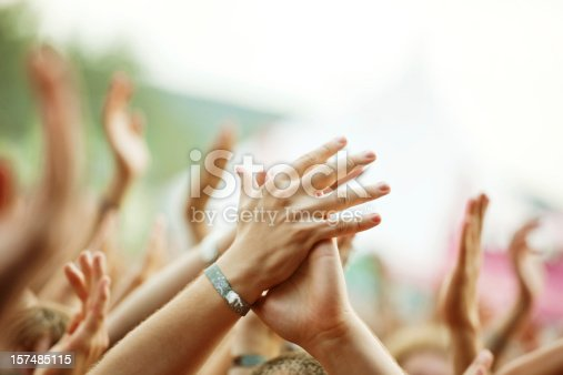 The hands of a concert crowd at a live music show, focus on the hand in the foreground