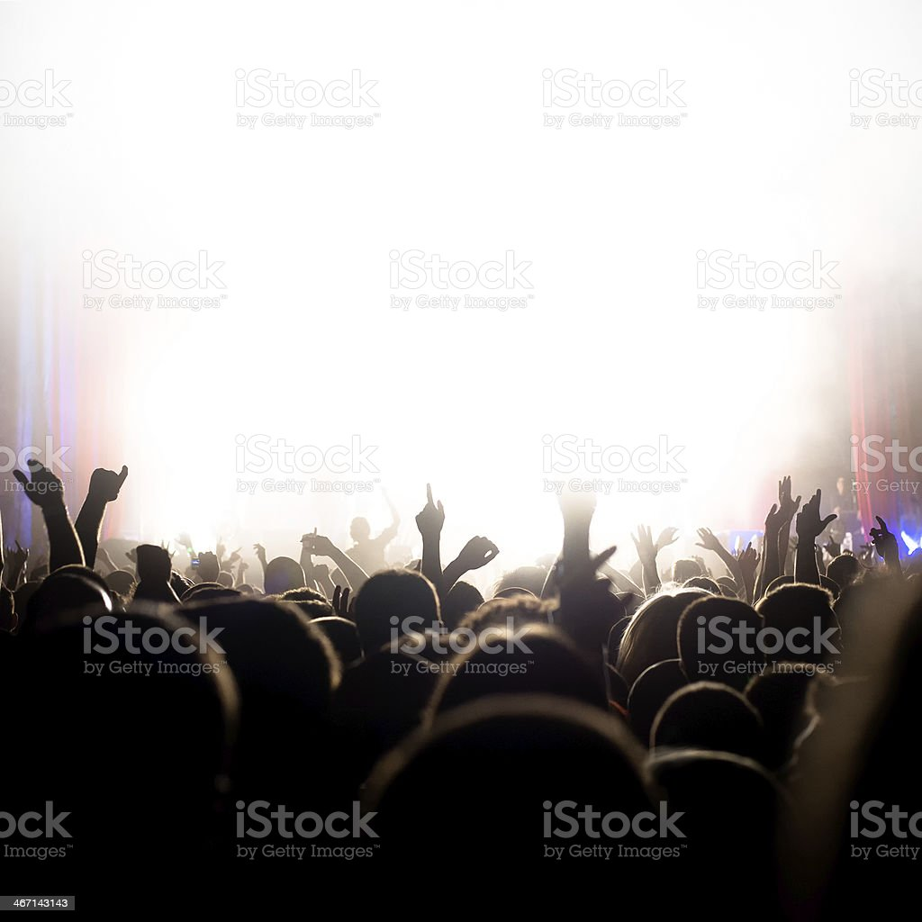 Crowd cheering and watching a band on stage.