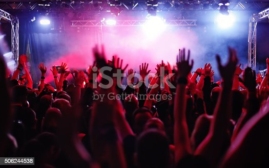 silhouettes of people on a rock concert raising hands
