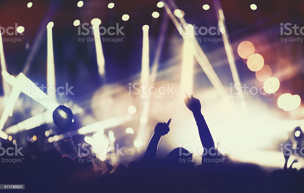 Rear view of people cheering at concert during music festival.Large...