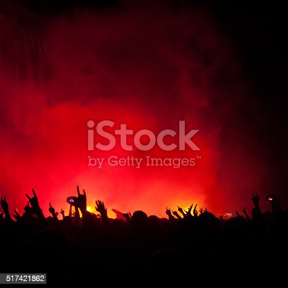 silhouettes of people on a rock concert raising hands, stage light in background.  NOTE - Some noise and artefacts visible due the use of high ISO because of difficult lighting conditions